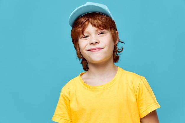 Rothaariger junge junge mit einem grinsen auf seinem gesicht blaue kappe gelbes t-shirt, das etwas schlechtes plant