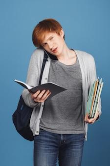 Rothaariger junger gutaussehender männlicher student in lässigem outfit mit schwarzem rucksack, der viele bücher und notizbuch in den händen hält und mit mutter am telefon spricht.