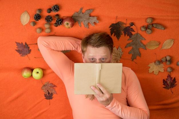 Rothaariger mann liegt auf einem orangefarbenen hintergrund und isst einen apfel. die großen rabatte für alle herbstkleidung für herren. junger süßer mann liegt auf einem holzboden mit herbstlaub und liest buch.