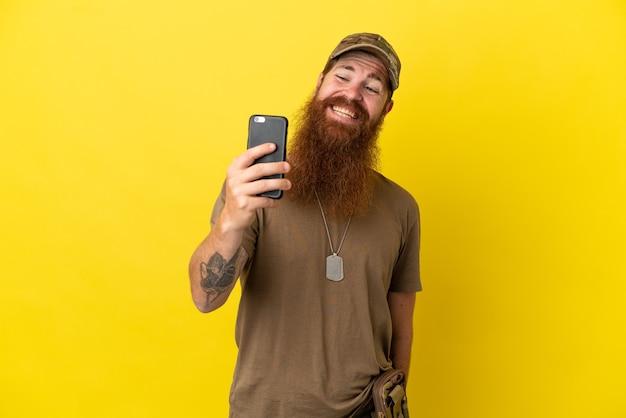 Rothaariger militärmann mit hundemarke auf gelbem hintergrund isoliert, der ein selfie macht