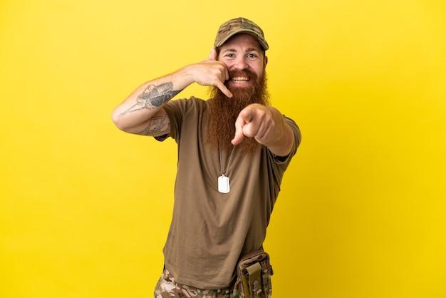 Rothaariger militärmann mit hundemarke isoliert auf gelbem hintergrund, der telefongeste macht und nach vorne zeigt