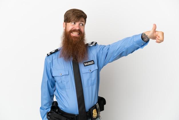 Rothaariger polizist isoliert auf weißem hintergrund, der eine geste mit dem daumen nach oben gibt
