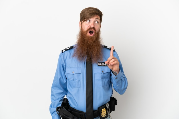 Rothaariger polizist isoliert auf weißem hintergrund, der eine idee denkt und mit dem finger nach oben zeigt