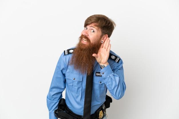 Rothaariger polizist isoliert auf weißem hintergrund, der etwas hört, indem er die hand auf das ohr legt