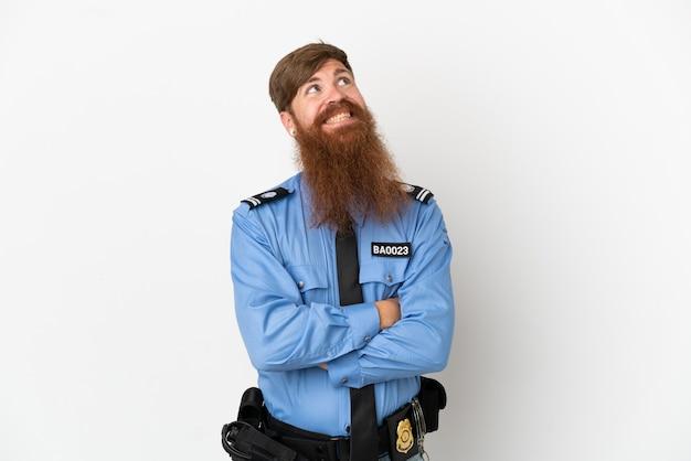 Rothaariger polizist isoliert auf weißem hintergrund, der lächelnd nach oben schaut