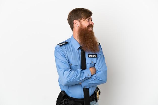 Rothaariger polizist isoliert auf weißem hintergrund, der seitlich schaut