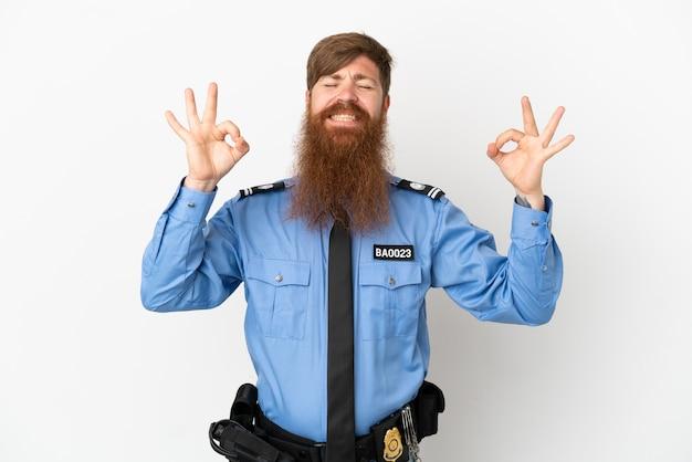 Rothaariger polizist isoliert auf weißem hintergrund in zen-pose