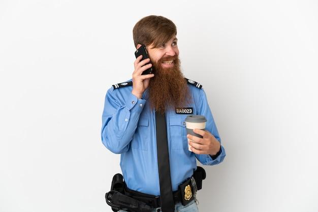 Rothaariger polizist isoliert auf weißem hintergrund mit kaffee zum mitnehmen und einem handy