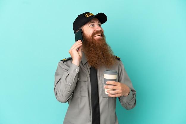 Rothaariger sicherheitsmann isoliert auf weißem hintergrund mit kaffee zum mitnehmen und einem handy