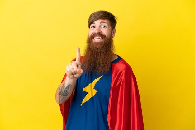 Rothaariger superheld-mann isoliert auf gelbem hintergrund, der einen finger im zeichen des besten zeigt und hebt