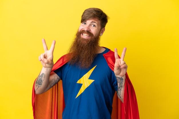 Rothaariger superheld-mann isoliert auf gelbem hintergrund, der victory-zeichen mit beiden händen zeigt