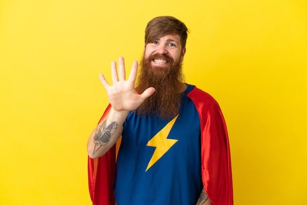 Rothaariger superheld mann isoliert auf gelbem hintergrund und zählt fünf mit den fingern