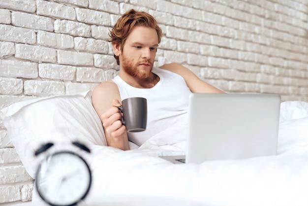 Rothaariges erwachen und liegt mit laptop im bett.