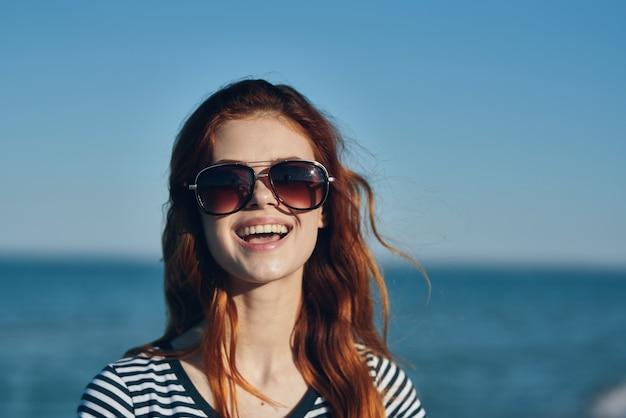 Rothaariges frauenmodell im t-shirt und im sonnenbrillenmeer im hintergrundsommerferien. hochwertiges foto