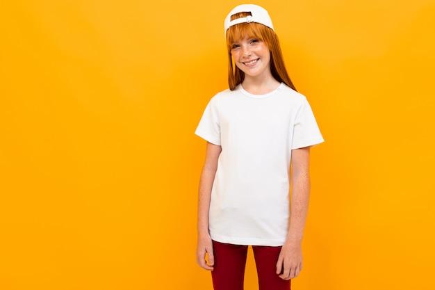 Rothaariges fröhliches mädchen auf einer orange in einem weißen t-shirt ohne inschriften