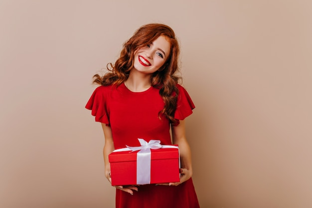 Rothaariges geburtstagskind lächelnd winsome weibliches modell im roten kleid, das weihnachtsgeschenk hält.