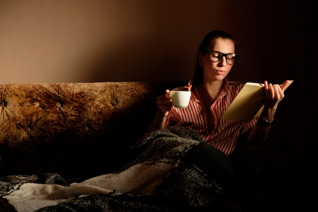 Rothaariges ingwermädchen im gestrippten hemd, das buch liest, kaffee trinkt, auf dem sofa liegt und lächelt