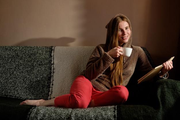 Rothaariges ingwermädchen im lustigen kapuzenpullover-lesebuch, kaffee trinkend, auf dem sofa liegend und lächelnd