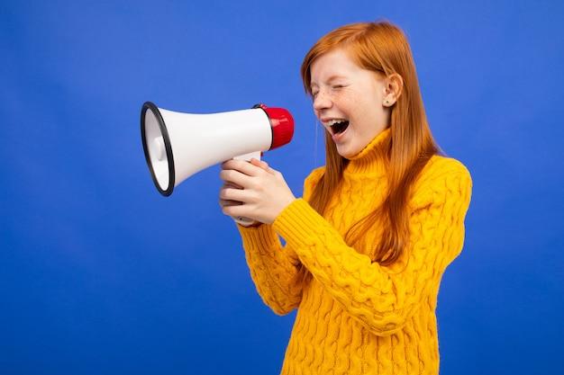 Rothaariges junges mädchen, das in einem blauen studio die nachrichten ins mikrofon ruft