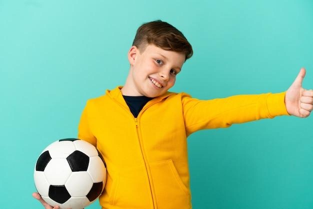 Rothaariges kind, das fußball isoliert auf blauem hintergrund mit daumen nach oben spielt, weil etwas gutes passiert ist?