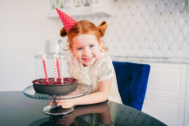 Rothaariges kind mädchen in einer roten mütze sitzt an einem tisch und lächelt in der nähe steht ein festlicher kuchen mit kerzen in einer hellen küche, geburtstag, lebensstil