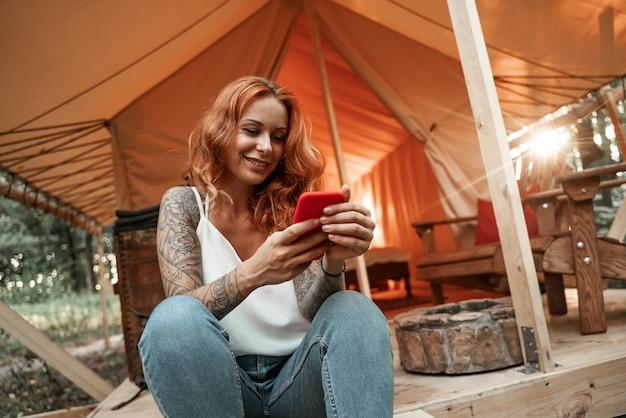 Rothaariges lächelndes mädchen sitzt neben dem zelt und chattet messaging-streaming auf dem smartphone, postet, mag in sozialen medien. reisen sie außerhalb der stadt im wald. camping.