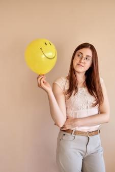 Rothaariges mädchen, das einen gelben ball mit einem lächeln auf einem beigen hintergrund hält