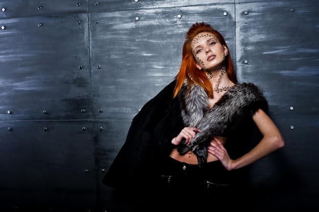 Rothaariges mädchen des mode-modells mit ursprünglich bilden wie leopard-fleischfresserabnutzung auf pelzen gegen stahlwand.
