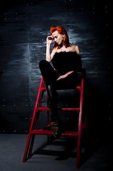Rothaariges mädchen des mode-modells mit ursprünglich bilden wie leopardraubtier gegen stahlwand. studioportrait auf strichleiter.