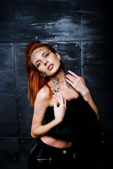 Rothaariges mädchen des mode-modells mit ursprünglich bilden wie leopardraubtier gegen stahlwand.