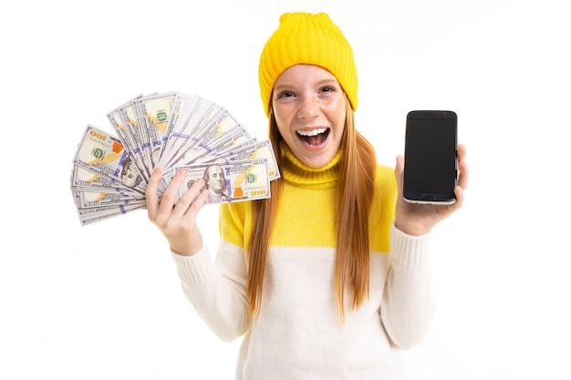 Rothaariges mädchen hält geld und ein telefon mit modellhänden auf weiß