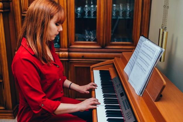 Rothaariges mädchen im roten hemd, das lernt, zu hause klavier zu spielen