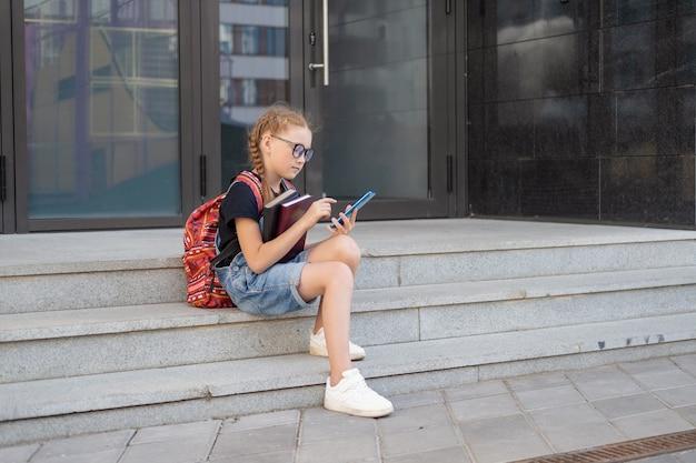 Rothaariges mädchen in brillen mit büchern und rucksack. setzen sie sich und tippen sie auf dem telefon. zurück zum schulkonzept.