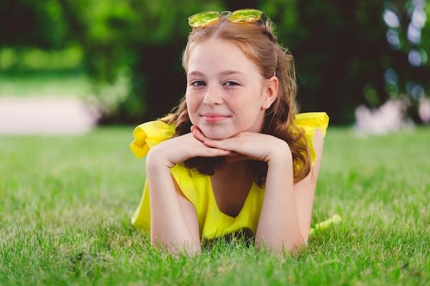Rothaariges mädchen in einem gelben kleid auf dem gras im park im sommer. foto in hoher qualität