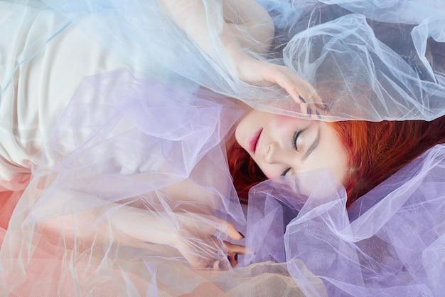 Rothaariges mädchen in einem hellen luftfarbenen kleid liegt auf dem boden, eine porträt-nahaufnahme. romantische frau mit langen haaren und wolkenkleid