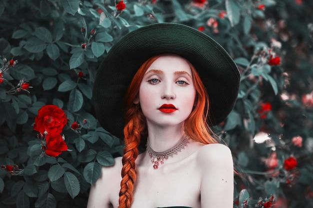 Rothaariges mädchen mit blauen augen und blasser haut in einem grünen hut und kleid mit einem roten gürtel. frau mit dem langen roten zopf vor dem hintergrund der buschpfirsichrosen. rote lippen