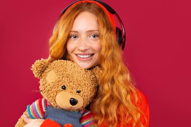Rothaariges mädchen mit einem bären. hört musik mit großen kopfhörern, posiert und lächelt. foto auf einer roten wand.