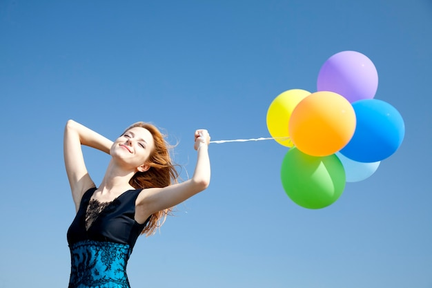 Rothaariges mädchen mit farbballons auf blauem himmel.