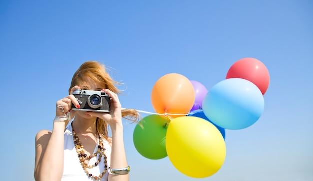Rothaariges mädchen mit farbballons und kamera auf blauem himmel.