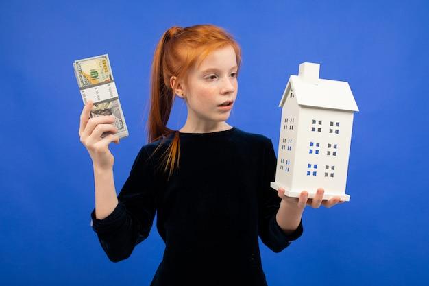 Rothaariges mädchen mit geld und einem haus auf blau. kauf einer immobilie