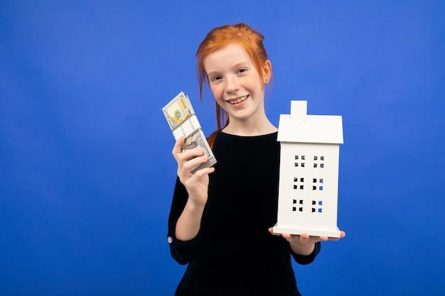 Rothaariges mädchen mit geld und einem modell eines hauses auf einem blauen hintergrund. kauf einer immobilie.