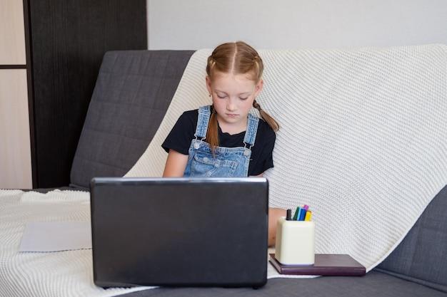 Rothaariges mädchen mit laptop während des studiums zu hause, fernbildungskonzept. zurück zum schulkonzept.