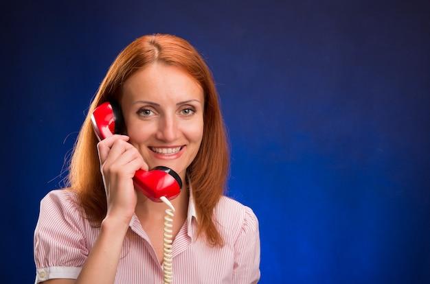 Rothaariges mädchen mit rotem telefon