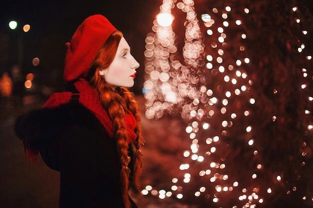 Rothaariges mädchen mit roten lippen in der roten baskenmütze und im schal, die gegen den hintergrund des weihnachtsbaumes stehen. farbiges bokeh. abstrakter hintergrund. goldene girlande. neujahrsnacht. kalter abend. kunst