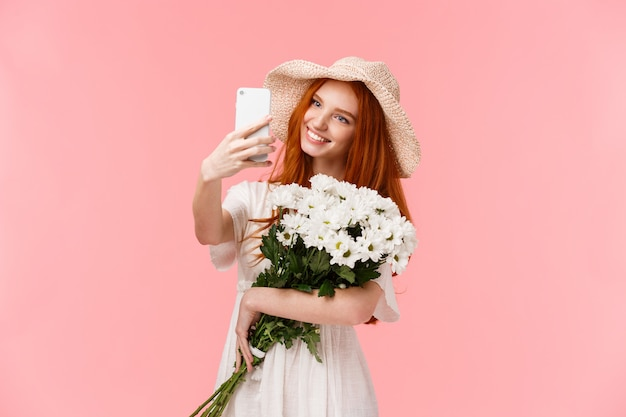 Rothaariges mädchen mit schönem blumenstrauß im weißen kleid, das selfie nimmt