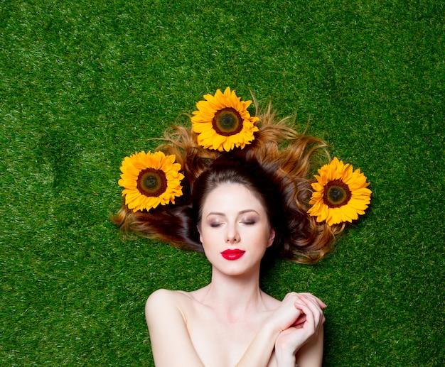 Rothaariges mädchen mit sonnenblumen auf gras