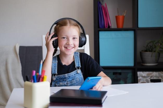 Rothaariges mädchen mit telefon beim lernen zu hause, fernunterricht spielen sie im handyspiel, schauen sie sich videos an.