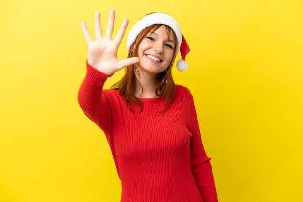 Rothaariges mädchen mit weihnachtsmütze auf gelbem hintergrund isoliert und zählt fünf mit den fingern