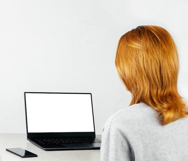 Rothaariges mädchen sitzt mit smartphone und laptop mit weißem modell