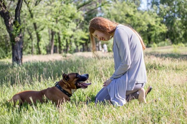 Rothaariges mädchen spielt mit einem hund im park